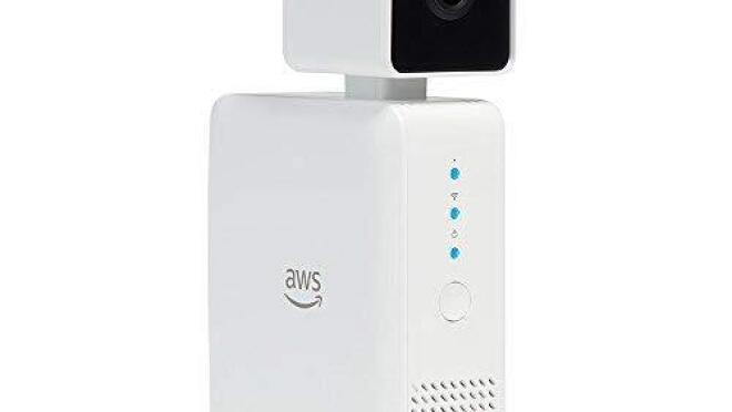 A device, consisting of a white box topped with a camera in a cube-shaped casing. The Amazon Web Services logo is on the side.
