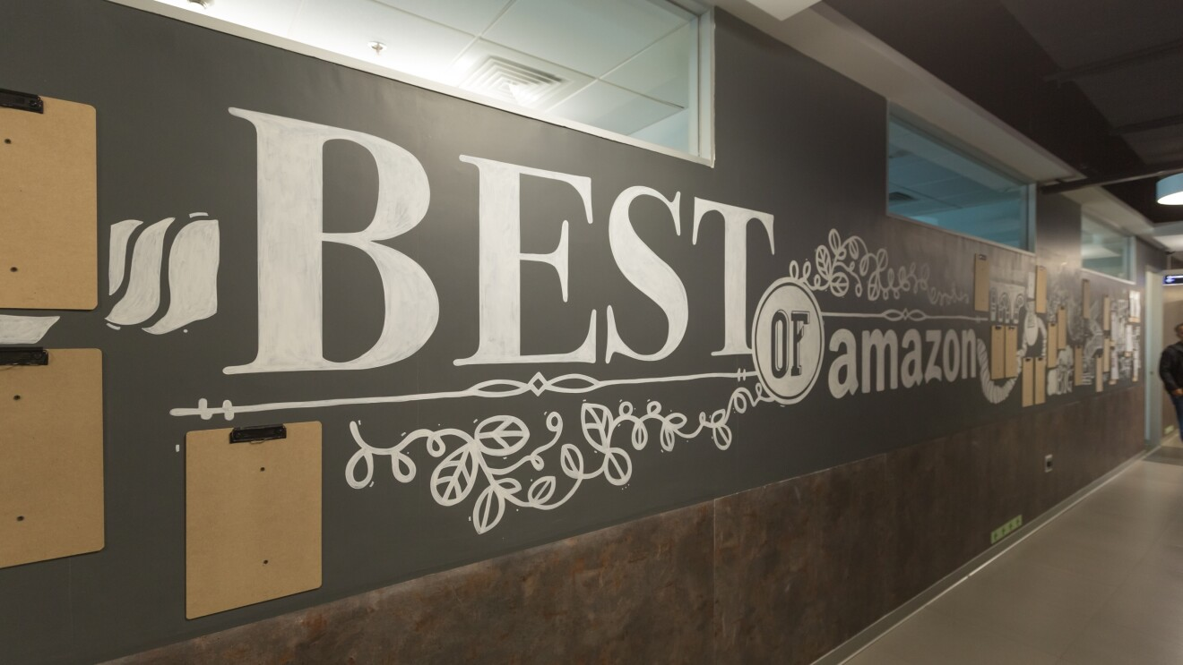"""The walls in an Amazon building that is painted with the words """"best of Amazon"""""""