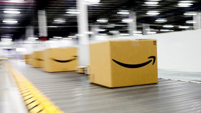 Amazon smile boxes move move along a conveyor belt within an Amazon Fulfilment Center or warehouse.
