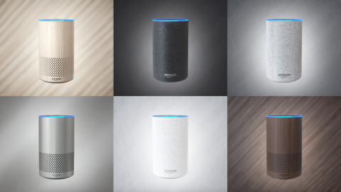 A selection of Amazon Echo devices in wood, black, grey, metallic silver, white, and dark brown.