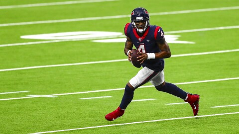 A photo of Deshaun Watson, quarterback of the Houston Texas, running with a football on a field during an NFL game.