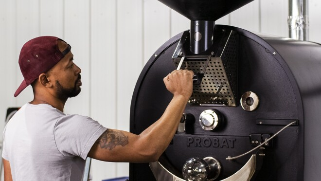 A man operating a coffee roasting machine.