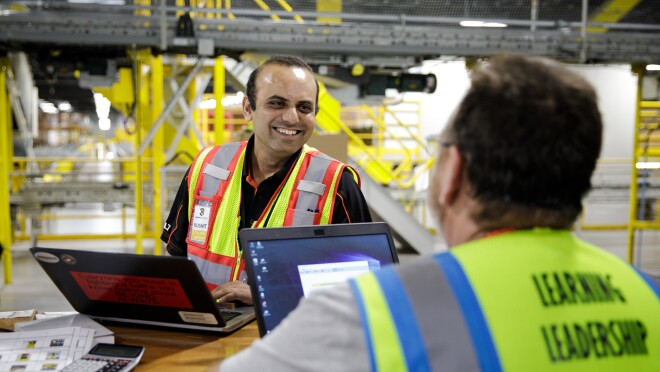 A man working at a laptop smiles at another man working at his own laptop. The two appear to be in conversation.