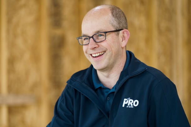 """A man wearing a navy polo short with """"Pro.com"""" embroidered on it, smiles. Behind him a home construction project."""
