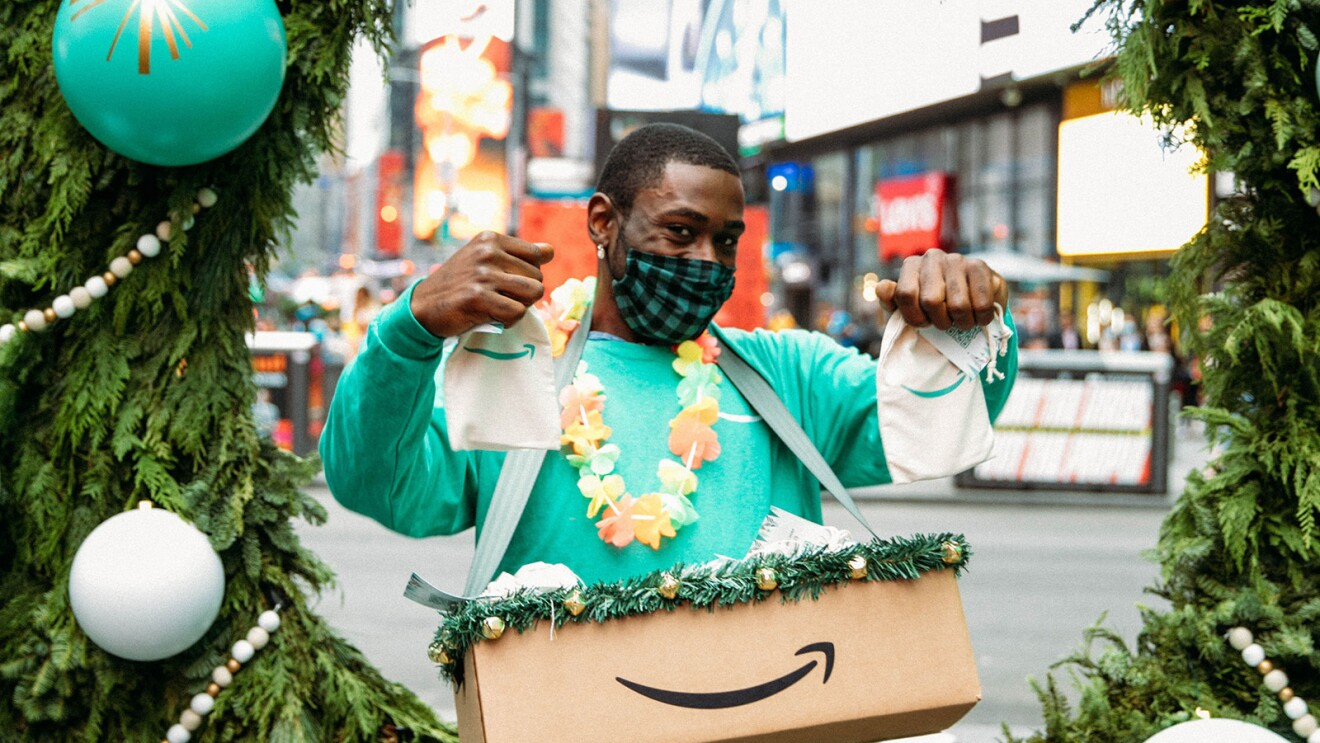 An image of a man smiling for a photo while wearing a mask. He is holding up two gift bags with the Amazon logo on them and has a box with the Amazon logo in front of him.