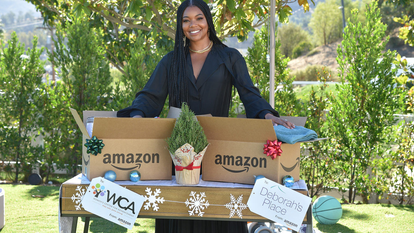 Gabrielle Union smiles for a photo in front of a table decorated with holiday decor that has two large Amazon boxes and two gift tags with nonprofit logos on it. She is outside with a green yard and trees around her.
