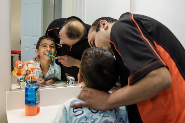 A man brushes a young boy's teeth in a bathroom.