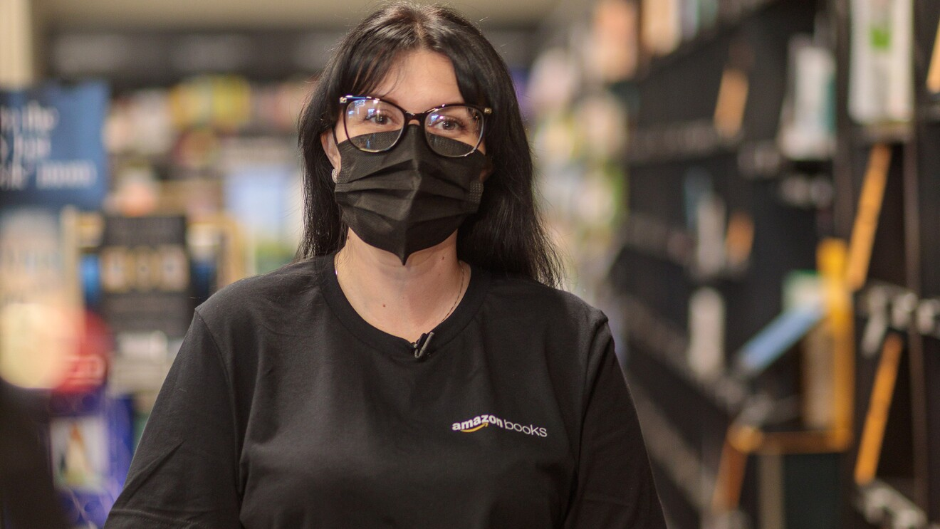 An image of a woman standing in an Amazon bookstore smiling for a photo under her mask.