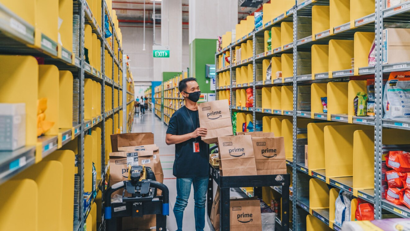 An employee packing multiple Amazon Fresh orders