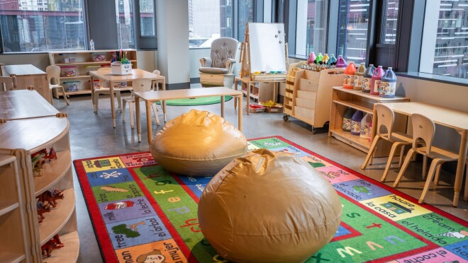 An image of a room with space for kids to play. There is a colorful mat on the floor, bean bags, other chairs, and toys for kids to play with.