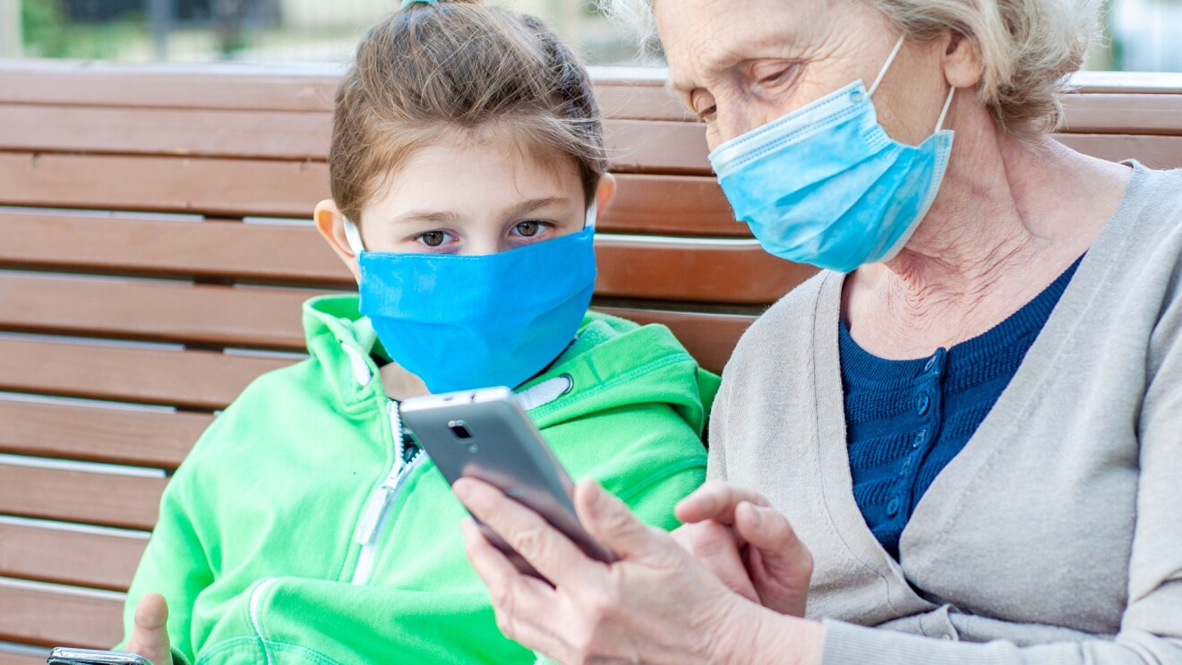 A grandmother sits with her granddaughter on a bench. They are both wearing masks and looking at the grandmother's phone.
