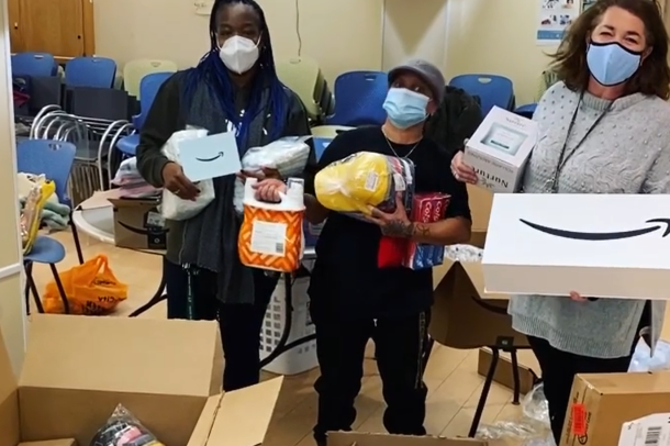 An image of women wearing masks and holding boxes of items donated to the charity they help support.