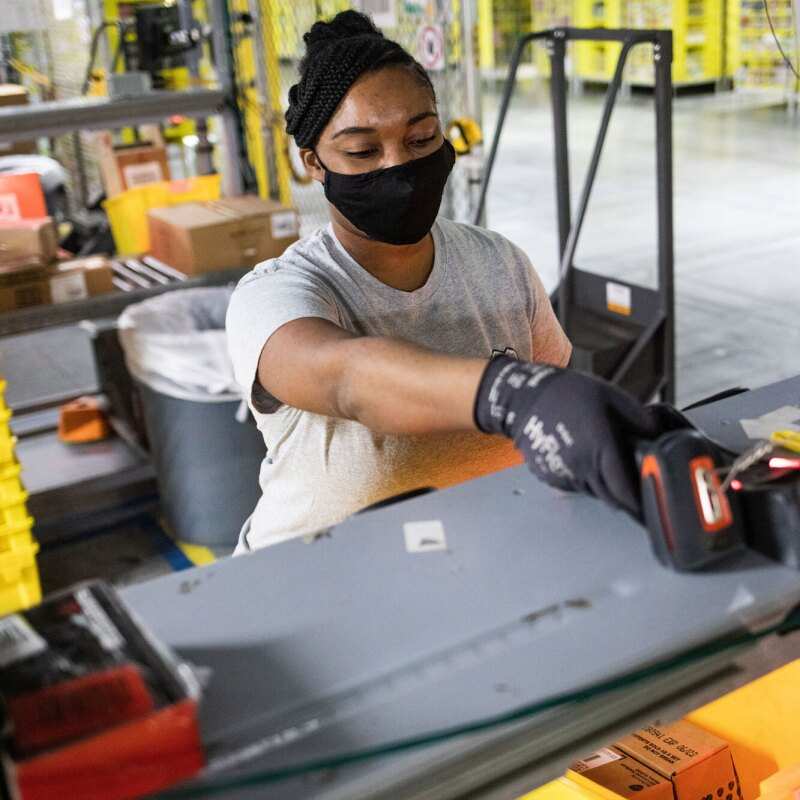 A woman wearing a face mask operates a scanning device inside an Amazon fulfillment center.