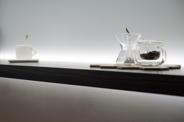 Three pieces of teaware sitting on a shelf. On the left is a white teacup with a cover adorned with a green leaf. On the  right are two glass teapots.