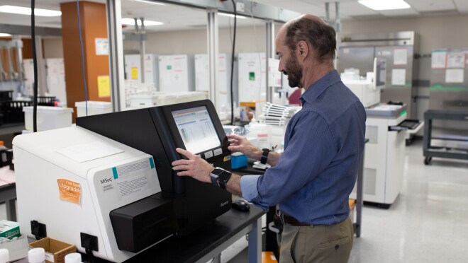 Michael Snyder, PhD, professor and chair of genetics for Stanford University's School of Medicine stands in front of a machine with a monitor in his lab. He wears three different smartwatches on his wrists.