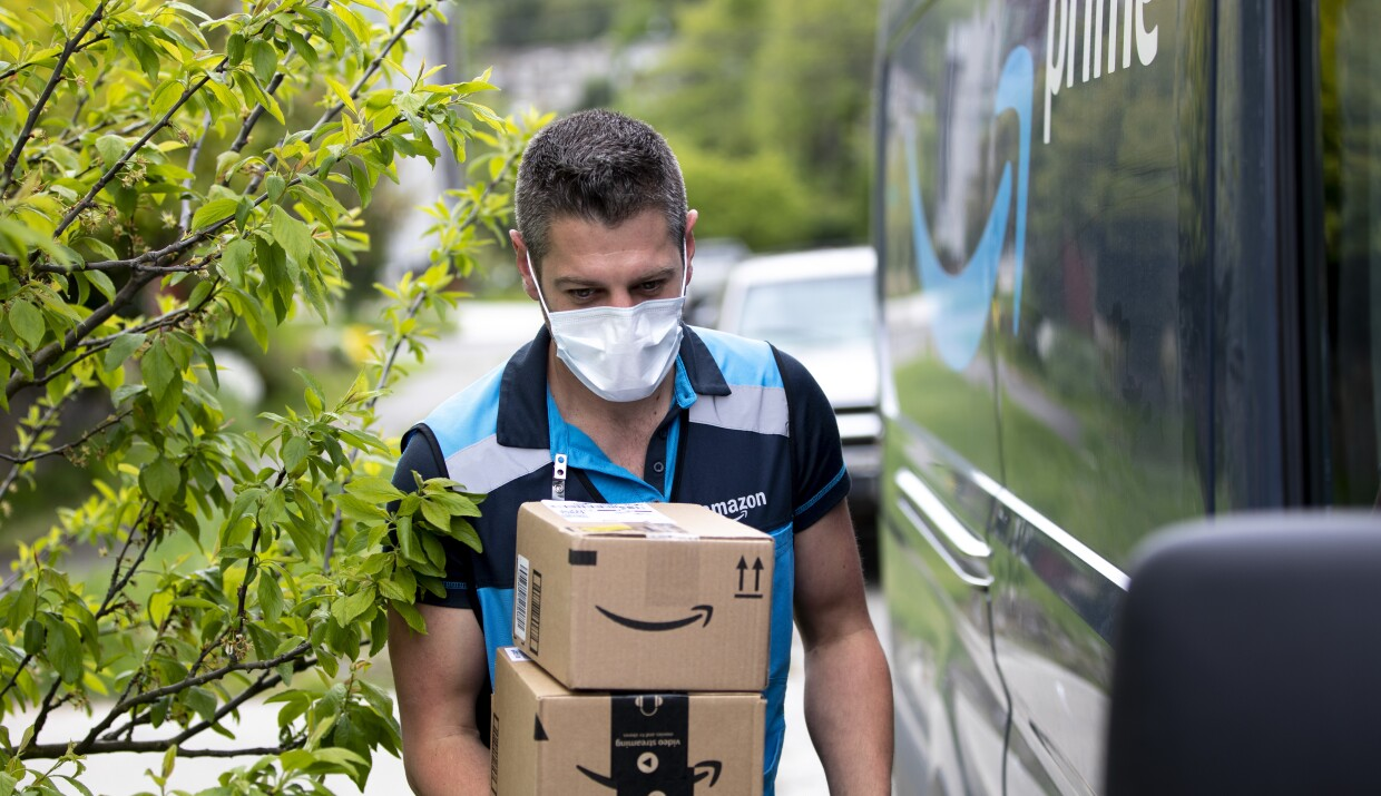 An Amazon delivery man walks along a Prime van carrying two Amazon boxes.
