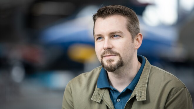 Portrait of man with airplane in background. The man has a goatee and wears a polo shirt and a jacket.