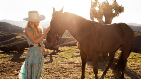 Jessica Simpson (singer, actress, author) stands in a field wearing cowgirl boots, a flowy dress, and belt, as she pets a horse on the muzzle in a promotional image