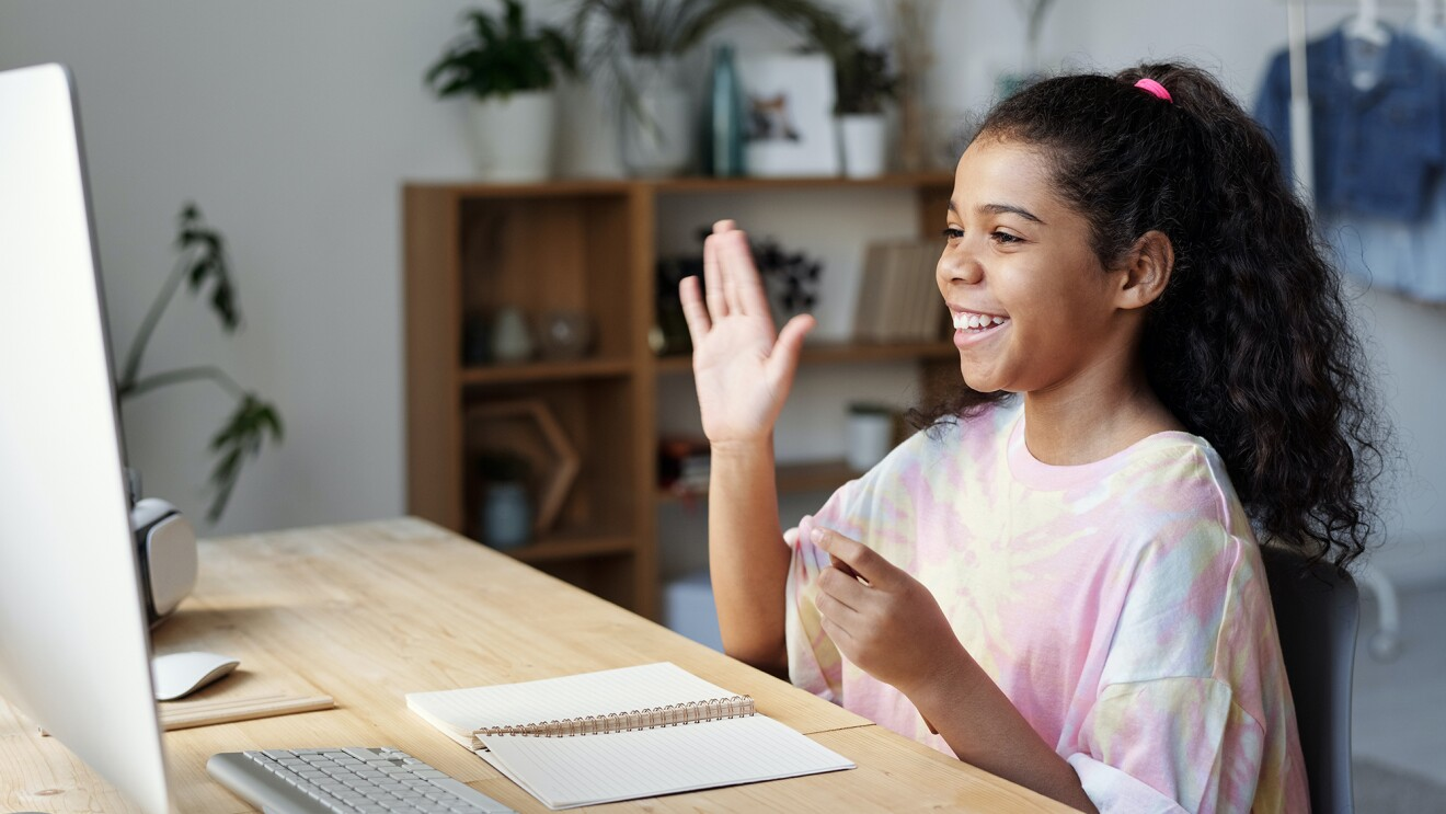 A young woman waves at her computer monitor as sheparticipates in a video chat.