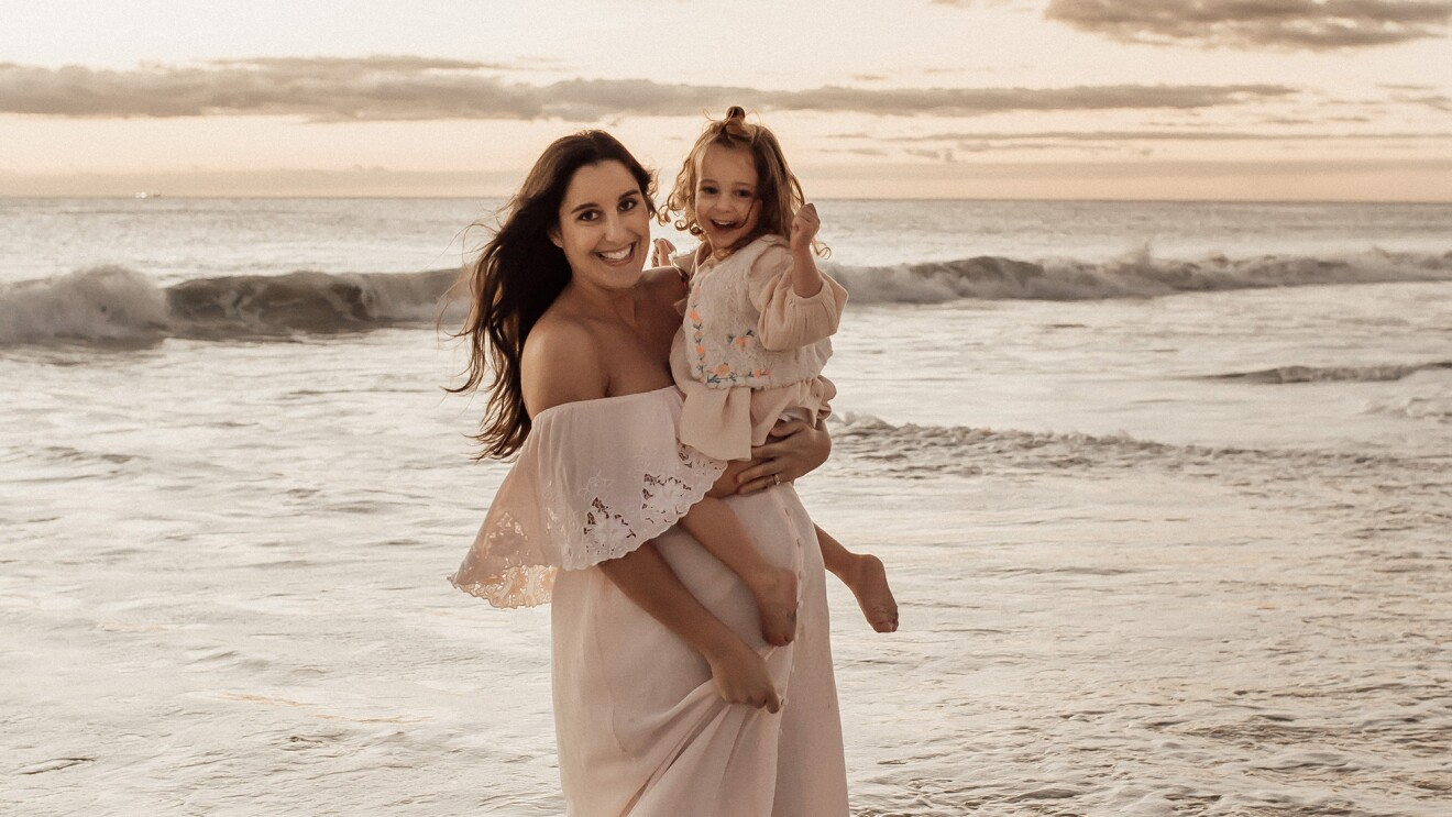 A woman stands on a beach wearing a white flowing dress, smiling for a photo while holding her child.
