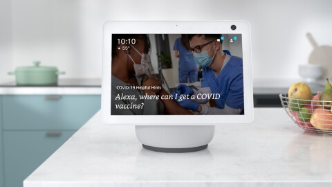 "An Alexa device sits atop a white kitchen countertop and the screen reads ""Alexa, where can I get a COVID-19 vaccine?"" There is a wire basket filled with pears, limes, and apples next to the device. In the background there is a seafoam colored pot on the stove."