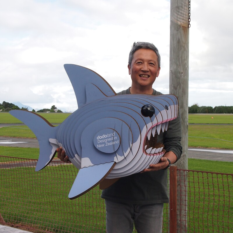 A man stands in a green space, holding a recycled cardboard shark.