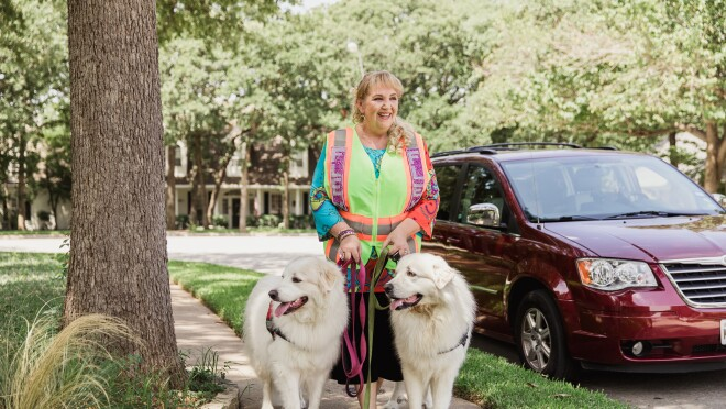A woman in a bedazzled Amazon Flex vest stands in front of her maroon mini-van. She is smiling at the camera and standing with her two white dogs, who are wearing service animal vests.