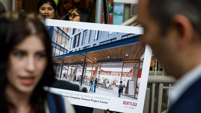 Andy Jassy speaks to a woman, in the background is a rendering of the future Center for Science and Innovation at Seattle University.