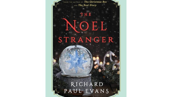 """Book cover for """"The Noel Stranger"""" shows a snow globe in the foreground with snow falling around a large crystal snowflake. In the background is garland, with Christmas lights, snow falls on the scene. The title is in red, with the author's name in white."""