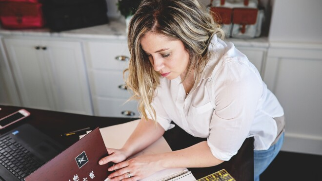 A woman wearing a white button down and blue jeans holds a fabric swatch book, examining the contents of the book. She leans over a desktop, which also holds her computer, notebook, and other office supplies.