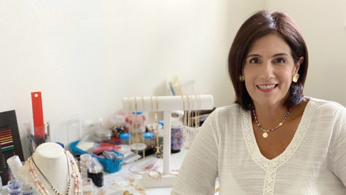 An image of a woman sitting in a white room with a jewelry-making stand in front of her.