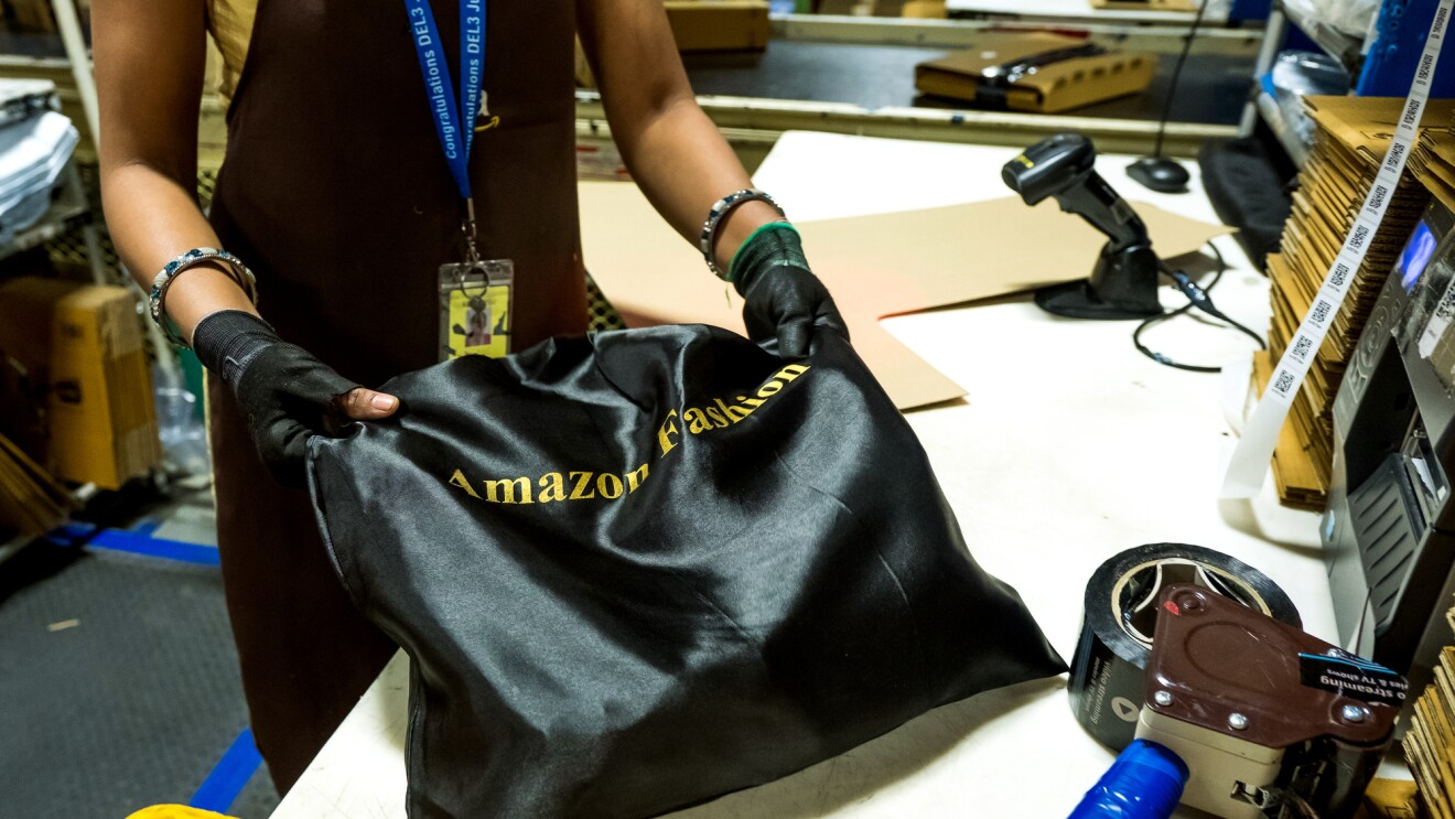 "A person photographed from the torso down holds a black satin bag labeled with the words ""Amazon Fashion."" The image also contains packing tape and a scanner. Boxes move along a conveyor belt in the background."