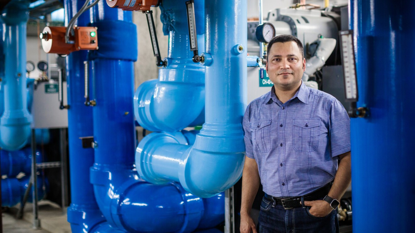 A man in short sleeved shirt and black pants stands among bright, blue-painted pipes of a waste-heat facility.