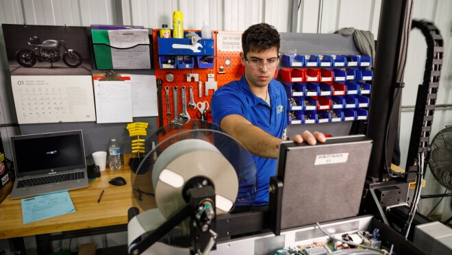 A man wearing safety glasses looks at a device that includes a spool that holds labels.