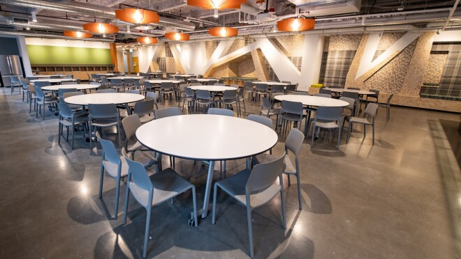 An image of a room with tables where families can eat together and enjoy a view of the city of Seattle.