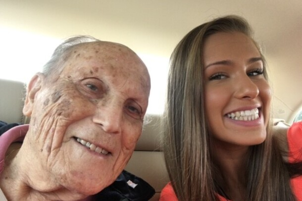 An image of a granddaughter taking a selfie with her grandfather in the car.