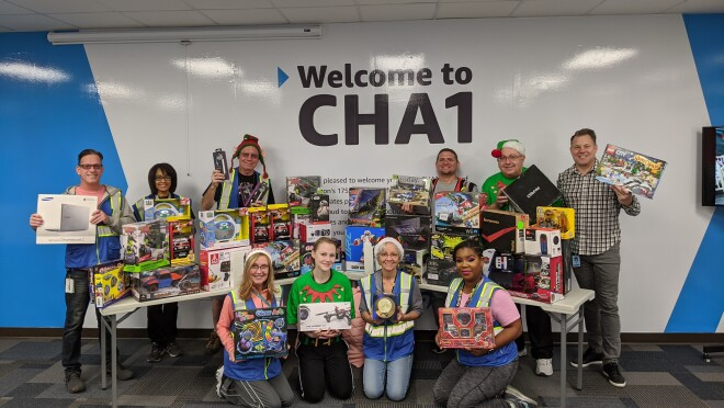 Amazon associates pose with toys raised for Ronald McDonald House