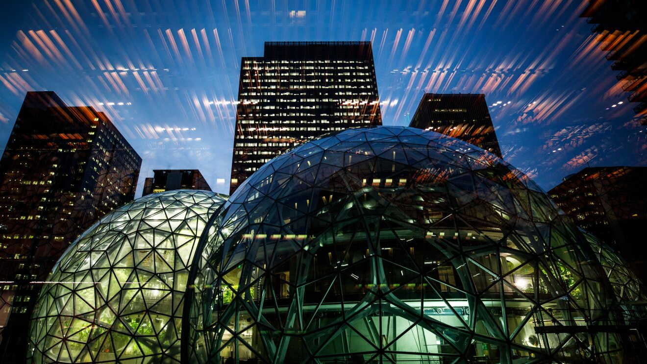 Amazon Spheres lit up at night, with lighting reflection in the glass.