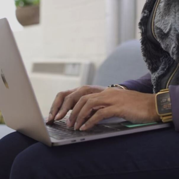 A woman types on the keyboard of a laptop computer, while sitting on a sofa.
