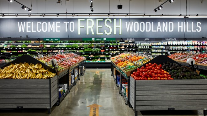 """Produce section of a grocery store with the words """"WELCOME TO FRESH WOODLAND HILLS"""" on the back wall."""