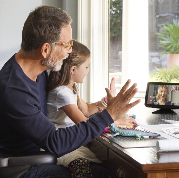 A little girl sits on a man's lap at a desk. They are both waving and looking at an Echo Show device, on which a woman is smiling and appears to be engaging with them.