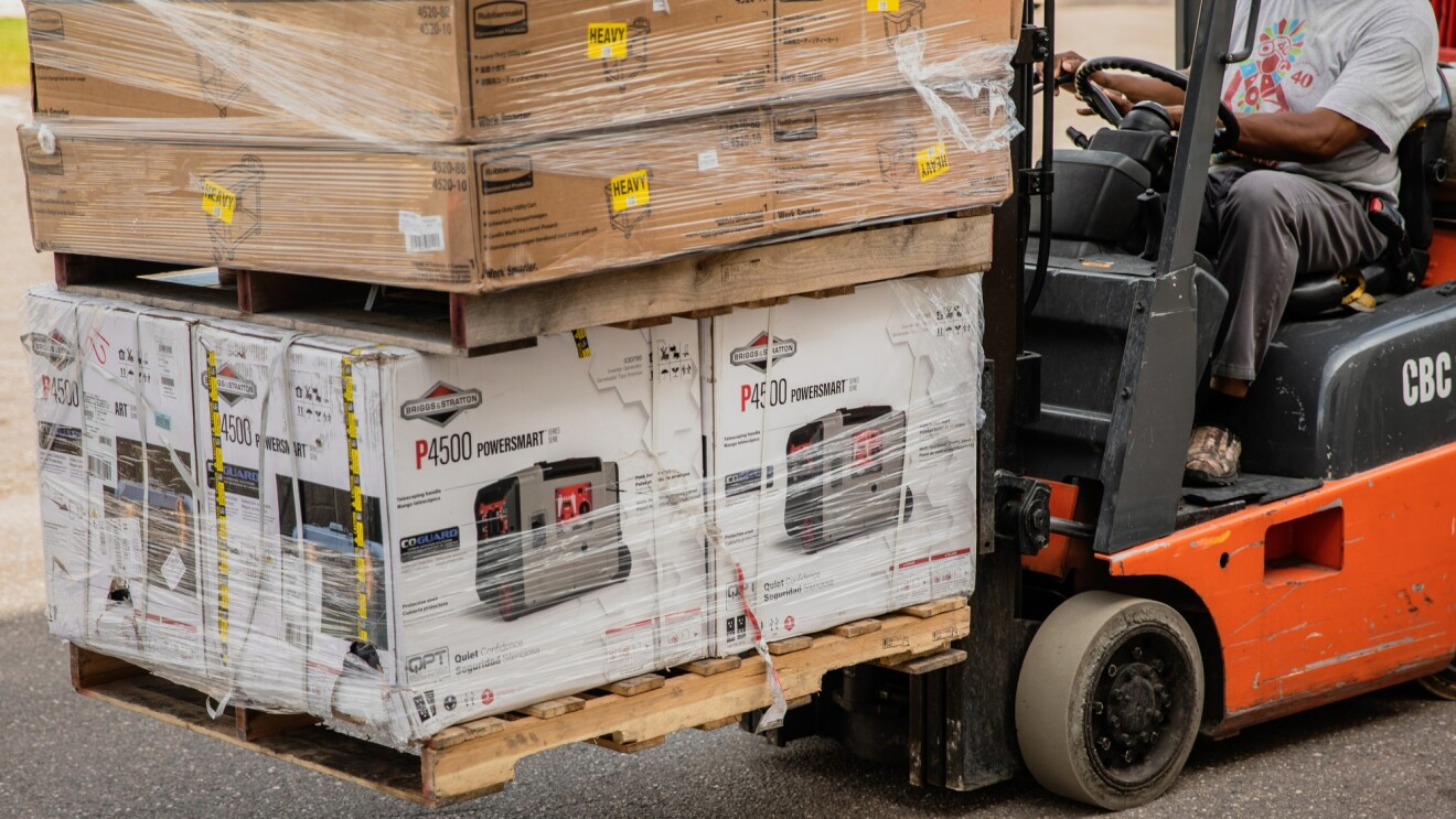 A man working with Amazon's disaster relief team is driving a forklift loaded with generators at the front. These generators will be used to provide power to those affected by recent natural disasters in the United States.