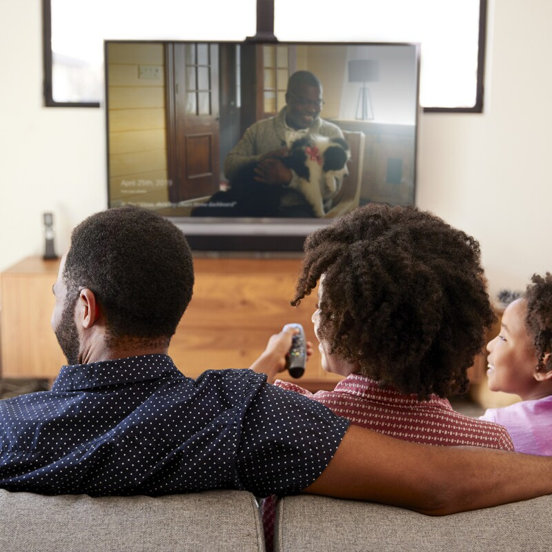 A family sits in front of a television, remote in hand. Two children and 2 adults smile as they click through photographs on the TV screen.