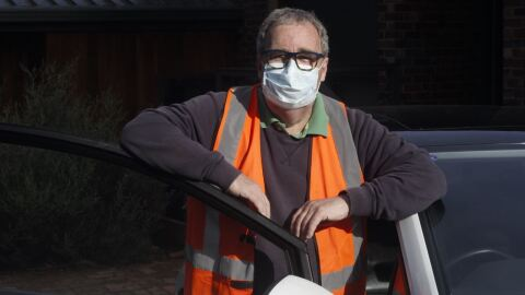 An image of a man next to his car smiling for a photo with a mask and an orange safety vest on.