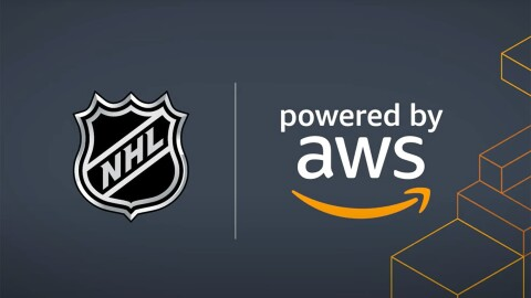 """An image with a dark blue background that displays the National Hockey League logo next to a text that says """"powered by AWS"""" with Amazon's smile logo below it. There are orange outlines of boxes on the right side of the image."""