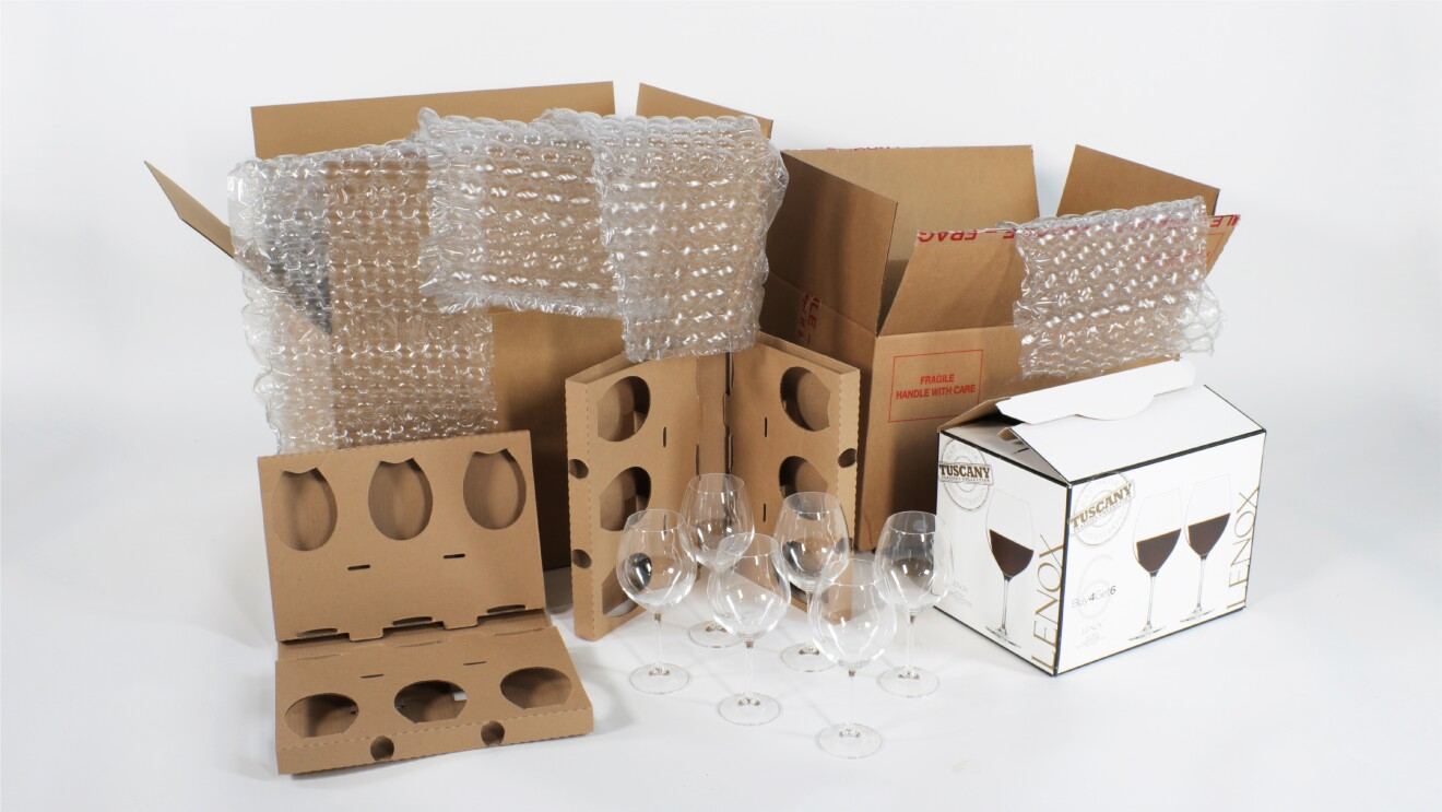 Image of multiple components of stemware packaging before the redesign laid out. Including 6 wine glasses, 2 cardboard inserts, the wine glass packaging, a large cardboard box, 4 sheets of bubble wrap, and a large amazon overbox.