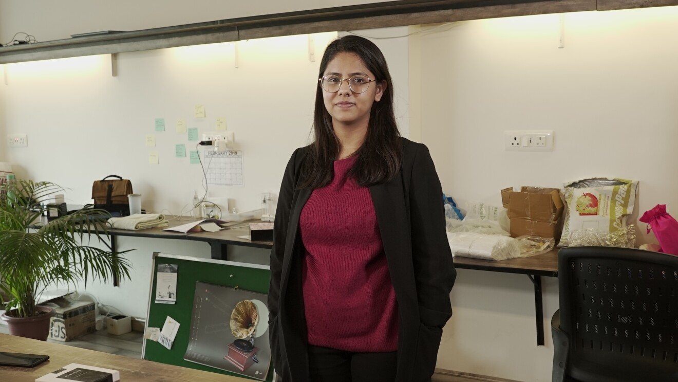 Tanvi Johri, creator of the all natural sanittary napkin, Carmesi, stands in her office wearing a tee-shirt and trousers topped with a jacket. Behind her is a long table with packages and huge potted plant stands to her right