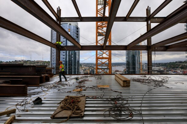 A construction worker walks across an under-construction Amazon skyscraper, with wires and support beams ready to be installed. Above him, another construction worker is on a steel support beam.