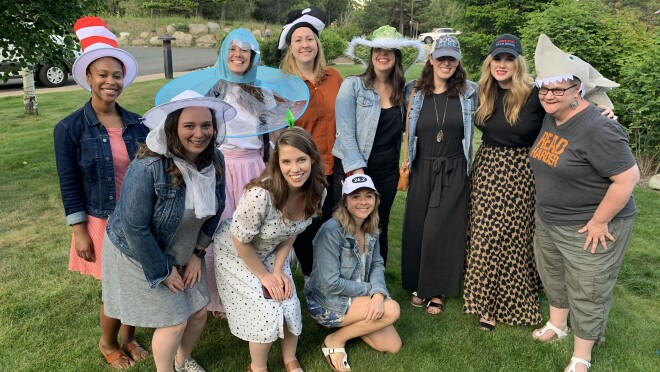 An image of Sarah with her team--all of them are smiling for a photo outside with fun hats on.