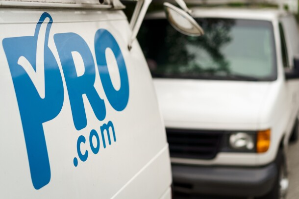 A Pro.com van, with the logo in the foreground of the image. Behind the van, another Pro.com van.